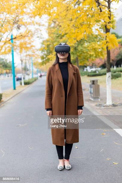woman wearing VR glasses on urban street