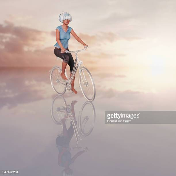 Woman wearing VR headset riding virtual bicycle rendered in glass with clouds and reflection