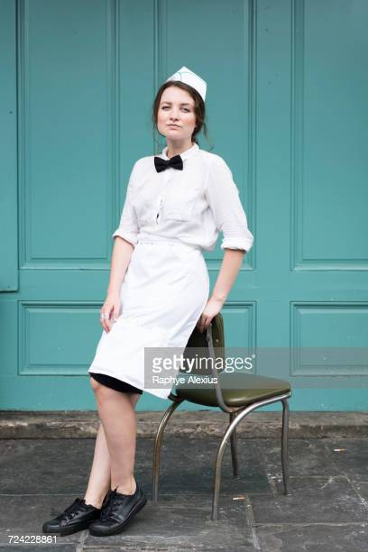 Woman wearing waitress uniform leaning against chair