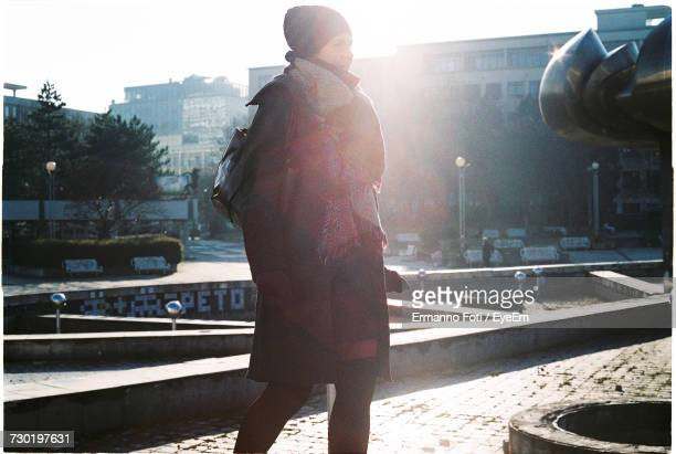 woman wearing warm clothing at park in city - 背景に人 ストックフォトと画像