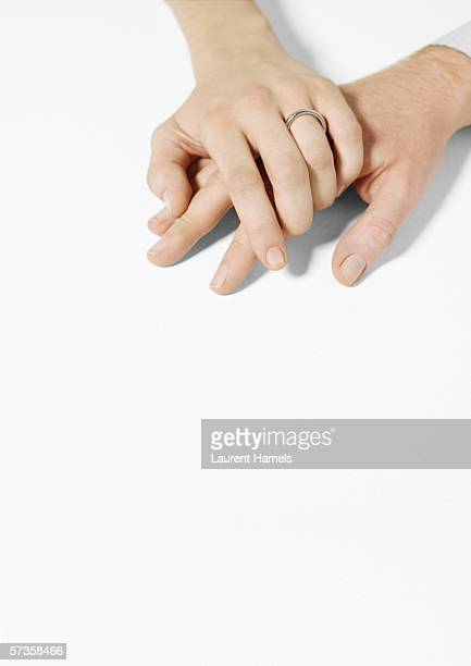 Woman wearing wedding ring clasping man's hand