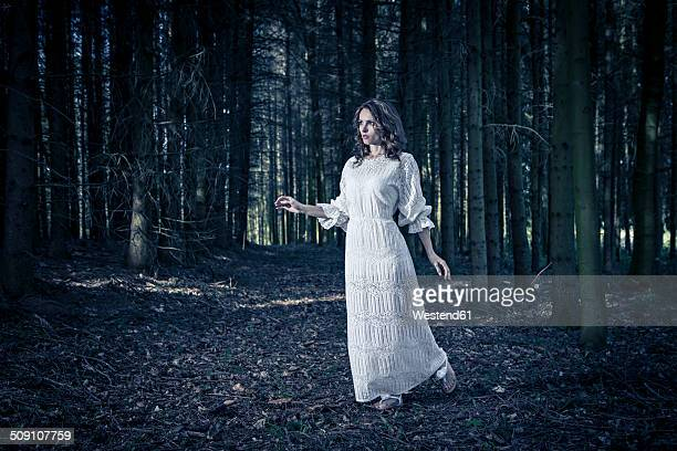 Woman wearing white dress in a forest