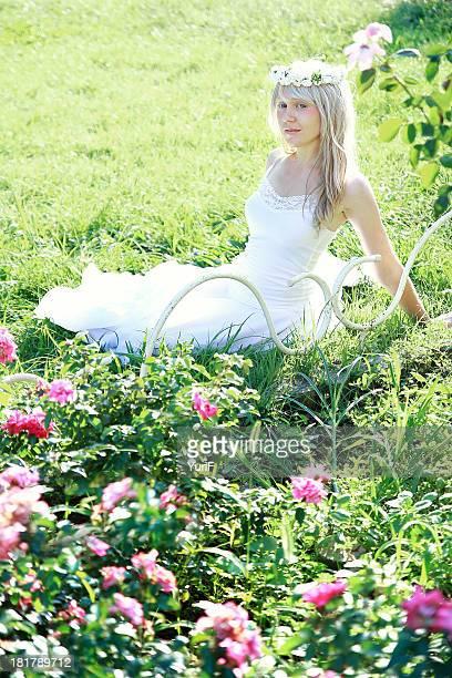 Woman wearing white dress on grass.