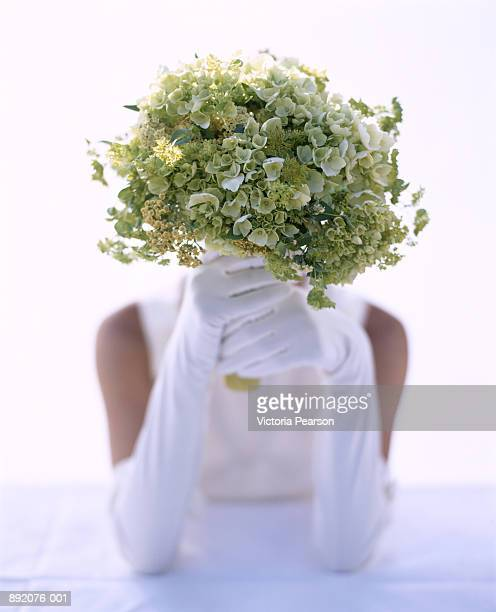 Woman wearing white gloves, holding green bouquet of flowers