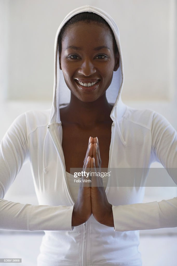 Woman wearing white hoodie in namaste pose : Foto de stock