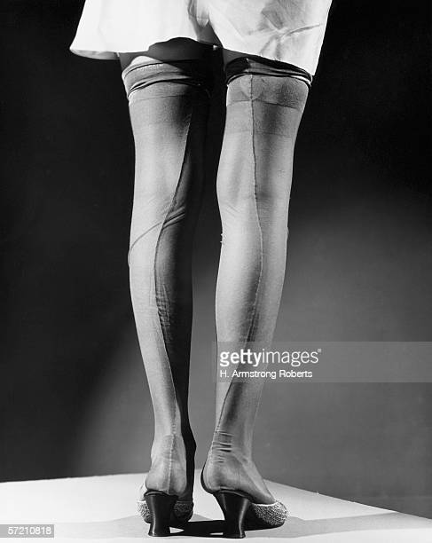 Woman wearing white slip and silk stockings low section