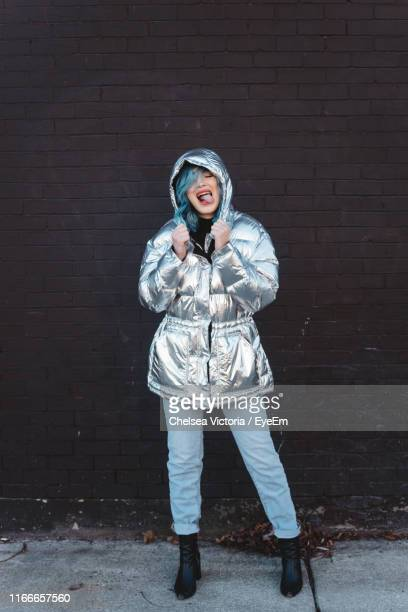 woman wearing winter jacket while standing against wall - gray pants stock pictures, royalty-free photos & images