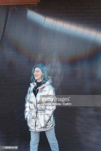woman wearing winter jacket while standing against wall - gray jacket stock pictures, royalty-free photos & images