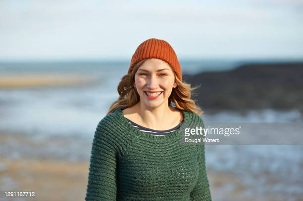 woman wearing wooly hat and jumper on autumn beach, portrait. - low tide stock pictures, royalty-free photos & images