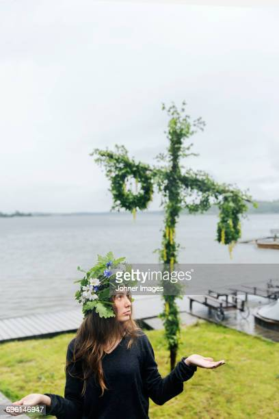 Woman wearing wreath with maypole on background