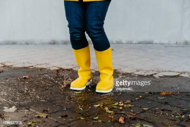 woman wearing yellow boots jumping on street - gummistiefel frau stock-fotos und bilder