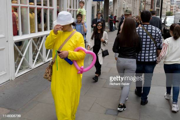 Woman wearing yellow carries a pink balloon in the crook of her arm, on 30th May 2019, in London, England.