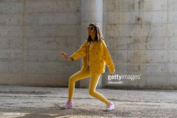 woman wearing yellow jeans clothes, dancing - yellow shoe stock pictures, royalty-free photos & images
