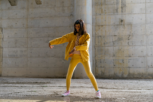 Woman wearing yellow jeans clothes, dancing - gettyimageskorea