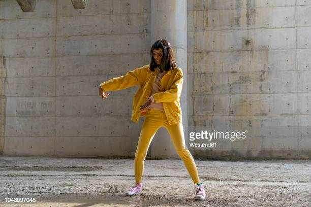 woman wearing yellow jeans clothes, dancing - mode stock-fotos und bilder