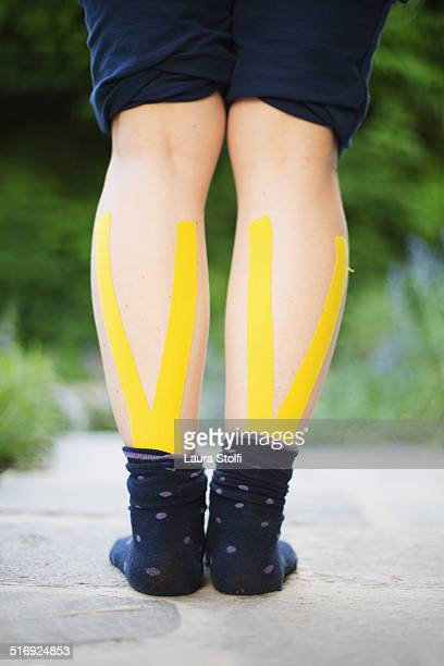 Woman wearing yellow kinesio tape on calf muscles