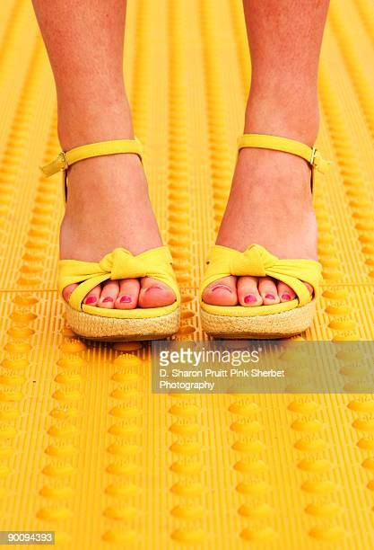 woman wearing yellow summer shoes on yellow - sandal stock pictures, royalty-free photos & images