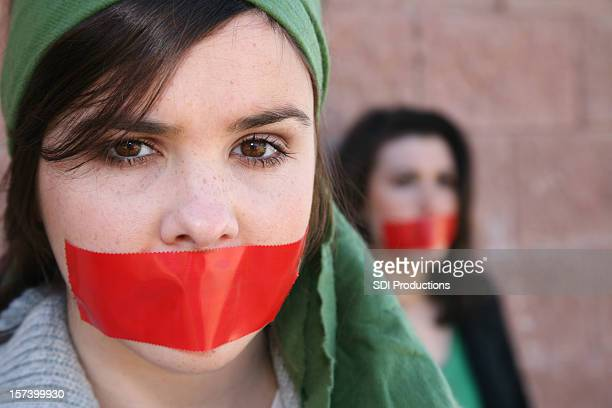 woman wearring a head scarf with red tape on mouth - protestor stock pictures, royalty-free photos & images