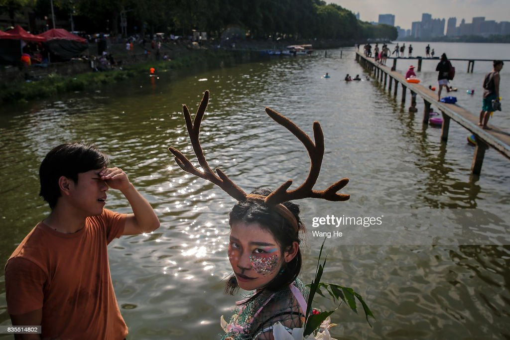 A woman wears a costume at East Lake on August 19, 2017 in Wuhan, Hubei province, China. This activity, which requires participants to ride their bikes and jump into the lake, attracts many extreme cycling enthusiasts from the city