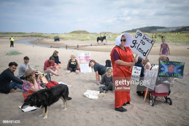 A woman wears a costume in the style of the 'Handmaid's Tale' on the beach as police patrol the area near Trump Turnberry Luxury Collection Resort...