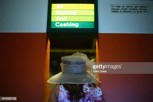 A woman wears a decorative hat places bets at a wagering window prior to the 150th running of the Belmont Stakes at Belmont Park on June 9 2018 in...