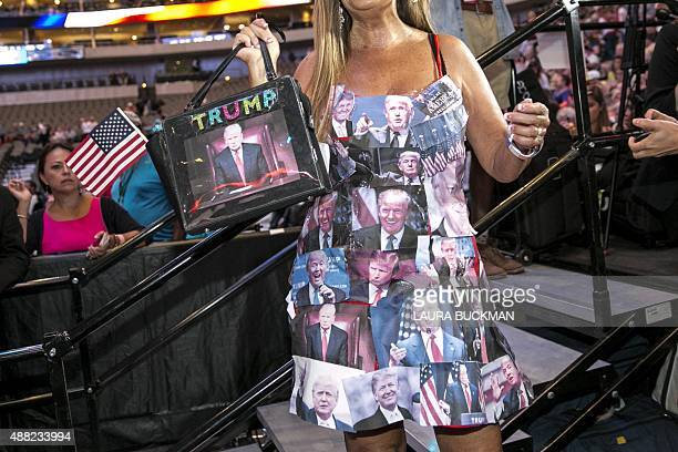 A woman wears a dress covered in printouts of US Republican presidential candidate Donald Trump's face during a campaign rally at the American...