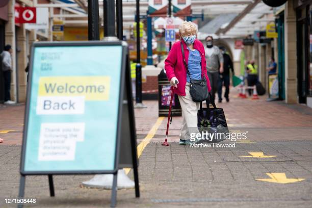 A woman wears a face covering and surgical gloves while walking down a 'shopping lane' in Castle Court shopping centre on September 9 2020 in...