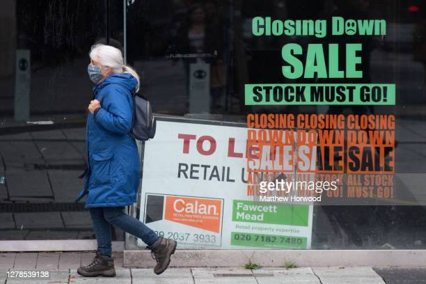 Woman wears a face covering as she walks past a closed shop on October 4, 2020 in Cardiff, Wales. A local lockdown came into force for Cardiff on...