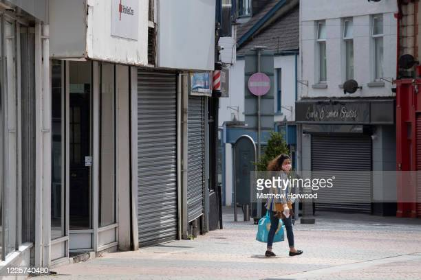 Woman wears a face mask and surgical gloves while carrying a bag and walking passed closed small businesses on High Street on May 18, 2020 in Merthyr...