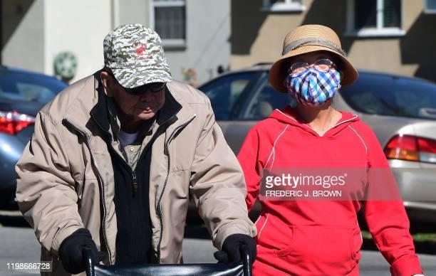 Woman wears a face mask as an elderly couple walk on a street in Alhambra, California on February 4, 2020. - As the coronavirus outbreak spreads,...