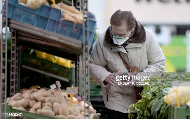 Woman wears a face mask as she shops vegetables at Meidlinger Markt market in Vienna on March 30 amid the novel coronavirus Covid-19 pandemic. /...