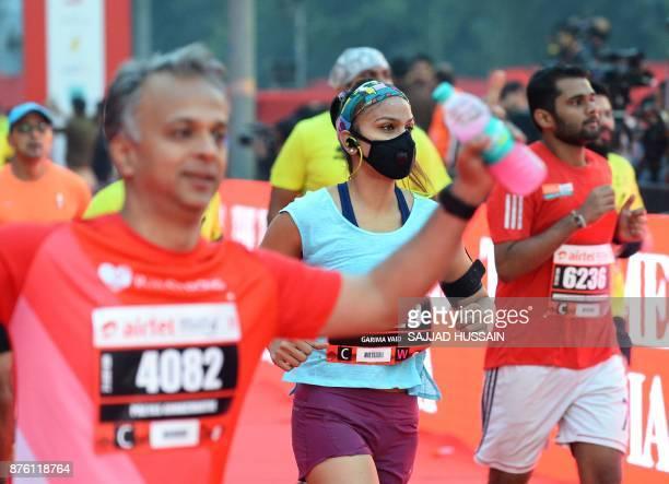 A woman wears a face mask as she takes part in the Airtel Delhi Half Marathon 2017 in New Delhi on November 19 2017 / AFP PHOTO / SAJJAD HUSSAIN