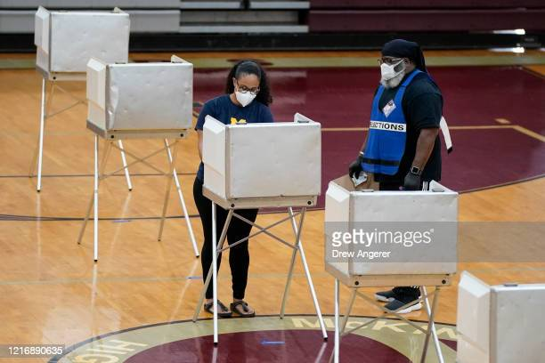 A woman wears a face mask as she votes at McKinley Technology High School on primary election day on June 2 2020 in Washington DC On Tuesday nine...