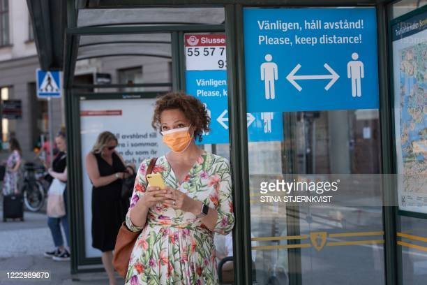Woman wears a face mask as she waits at a bus stop with an information sign asking people to keep social distance due to the coronavirus COVID-19...