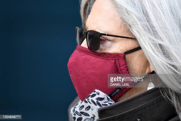 Woman wears a face mask as she walks along a street in central London on March 2, 2020. - Britain's Prime Minister Prime Minister on Monday chaired...