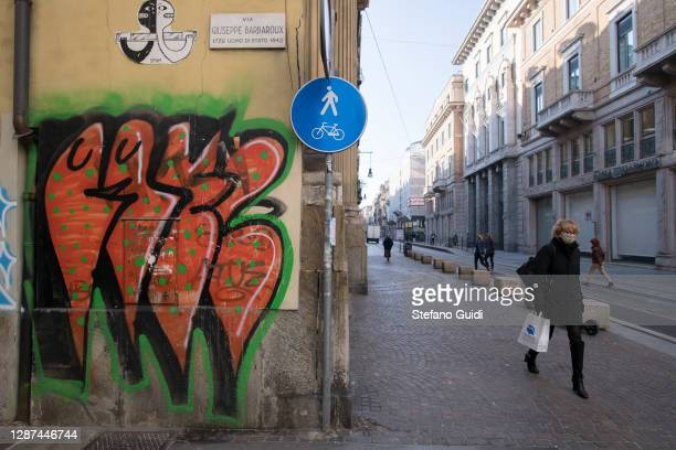 A woman wears a face mask as she walks in Via Barbaroux on November 24 2020 in Turin Italy Via Barbaroux is an old area in Turin which has been...