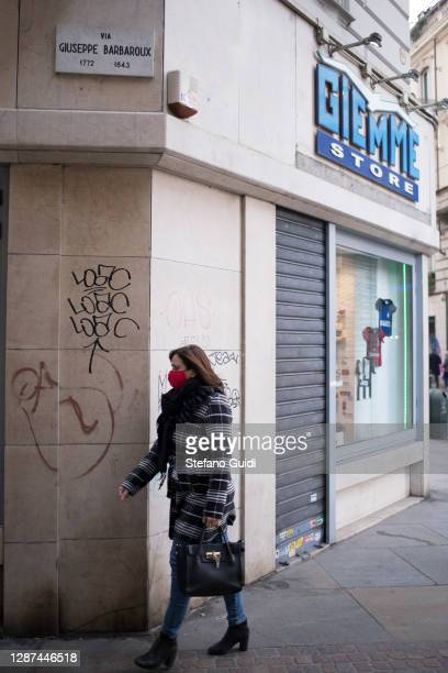 A woman wears a face mask as she walks past a closed shop in Via Barbaroux on November 24 2020 in Turin Italy Via Barbaroux is an old area in Turin...