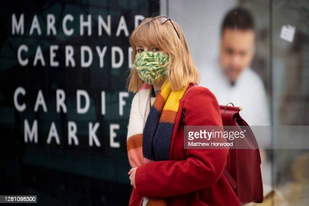 Woman wears a face mask as she walks past a sign for Cardiff Market on October 19, 2020 in Cardiff, Wales. Wales will go into a national lockdown...