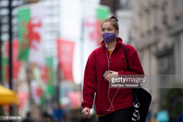 Woman wears a face mask as she walks up St. Mary Street on October 19, 2020 in Cardiff, Wales. Wales will go into a national lockdown from Friday...