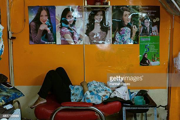 A woman wears a face mask in a local beauty salon in the wet market on April 9 2014 in Phnom Penh Cambodia The Cambodia beauty industry continues to...