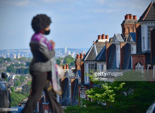 Woman wears a face mask in a residential street, Muswell Hill, North London, England on May 14th, 2020