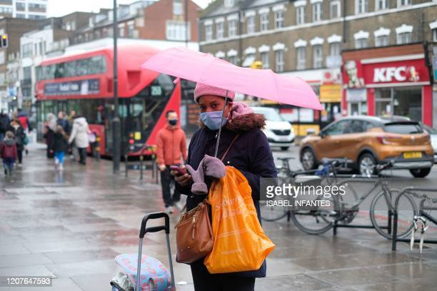 Woman wears a face mask in the street while out shopping in Finsbury Park, north London on March 19, 2020. - Britain's supermarkets stepped up...