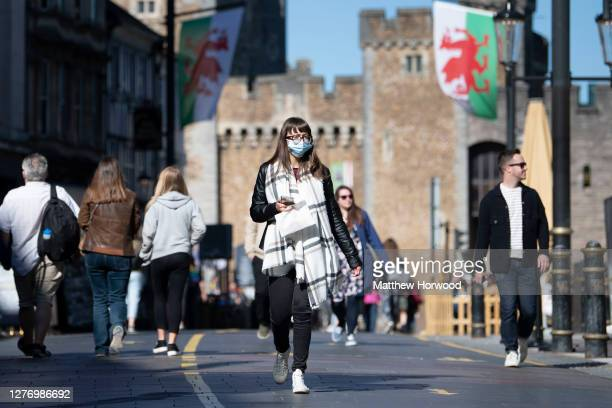 A woman wears a face mask near Cardiff Castle on September 27 2020 in Cardiff Wales A local lockdown will come into force for Cardiff and Swansea...