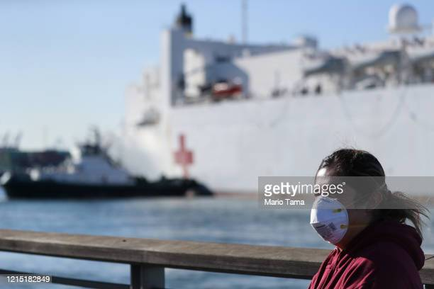 A woman wears a face mask near the USNS Mercy Navy hospital ship after it arrived in the Port of Los Angeles to assist with the coronavirus pandemic...