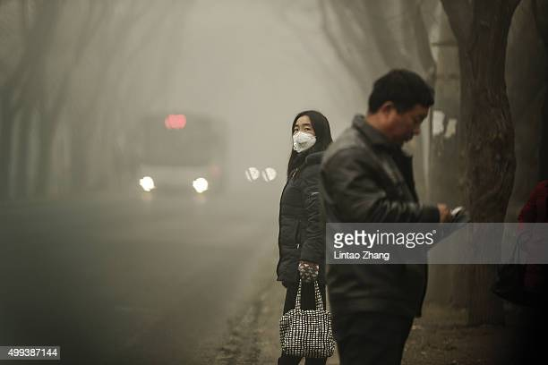 A woman wears a face mask next to traffic shrouded in heavy smog on December 1 2015 in Beijing China China's capital and many cities in the northern...
