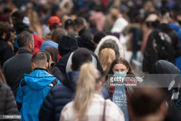 Woman wears a face mask on a busy Queen Street on November 21, 2020 in Cardiff, Wales. Restrictions across Wales have been relaxed following a...