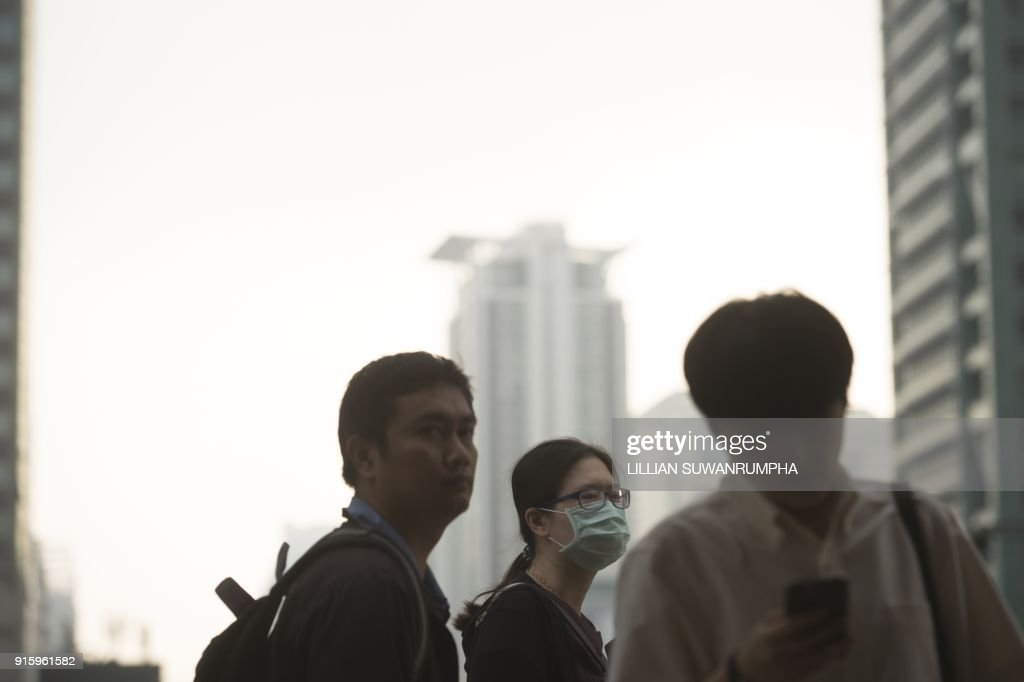 A woman wears a face mask on her way to work in the business district of Bangkok on February 9, 2018. The Pollution Control Department advised those with respiratory diseases to take precautions whilst outdoors on February 8, due to the highest PM indexes seen in recent days. /