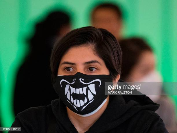Woman wears a face mask to protect against the COVID-19 after arriving at the LAX airport in Los Angeles, California on March 5, 2020. - California...