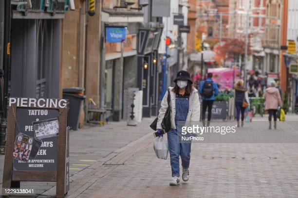 Woman wears a face mask walks in Nottingham on 28 October 2020.