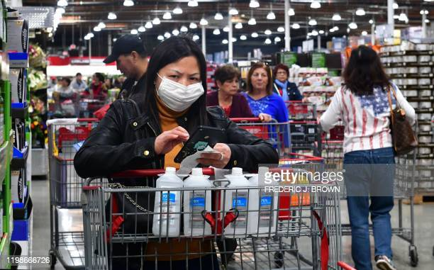 A woman wears a face mask while purchasing bottles of rubbing alcohol at a Costco store in Alhambra California on February 4 2020a Home Depot store...